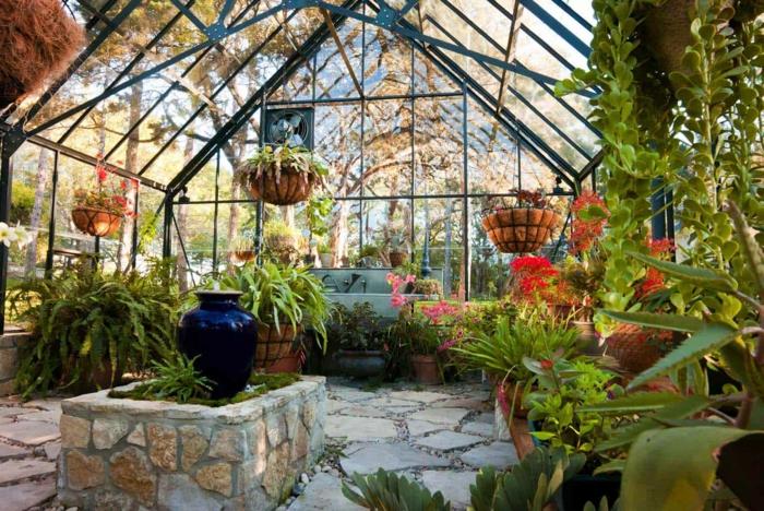 jardin dans véranda, sol en pierre, verrière avec pots suspendus et plantes, pot d'argile