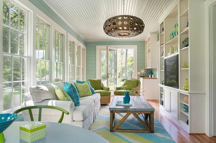 veranda style bord de mer, table basse bois, sofas et table de repas ronde, plafonnier rotin