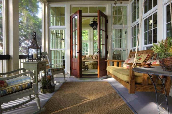 amenager une veranda blanche, tapis sisal, chaise de relaxation, meubles rétro, banquette suspendue