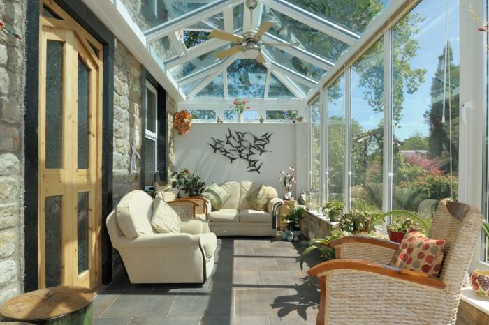 jolie véranda donnant vers le jardin, toiture vitrée, chaises en rotin, sofas blancs, grande porte en bois