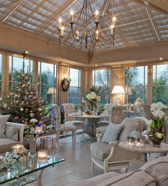 aménagement de véranda, chandelier rustique, sapin décoré de jouets et d'ampoules, grand salon style anglais
