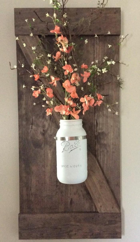 vase blanche avec fleurs oranges accrochés à un panneau en planches de bois