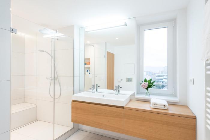 Fenetre qui donne de lumière naturelle, vase avec fleur, idée carrelage salle de bain, robinetterie et lavabo modernes
