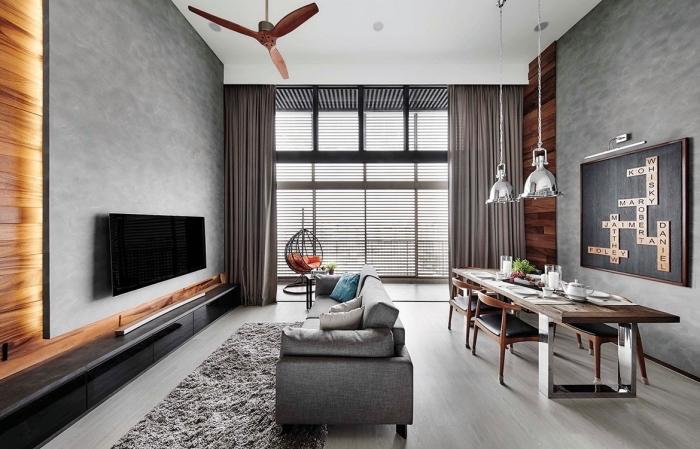 idée meuble style industriel pour salon, modèle de canapé gris sur plancher bois gris clair, revêtement mural panneaux bois