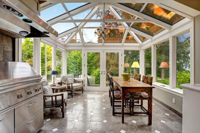 veranda cuisine, table de repas en bois, construction victorienne, chandelier, aménagement de véranda contemporaine