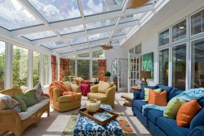 jolie véranda blanche, sofa bleu, coussins colorés, verrière de toit, sofas beiges, ottomane bleu et blanc