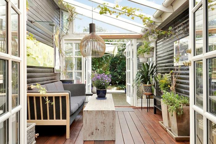 amenagement de veranda interieur, sol en poutres de bois, sofa gris, verrière dr toit pour veranda fermée