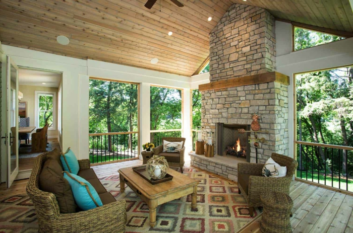 aménagement véranda style rustique, table basse bois, coussins bleus et beiges, sofa rotin, cheminée en pierre