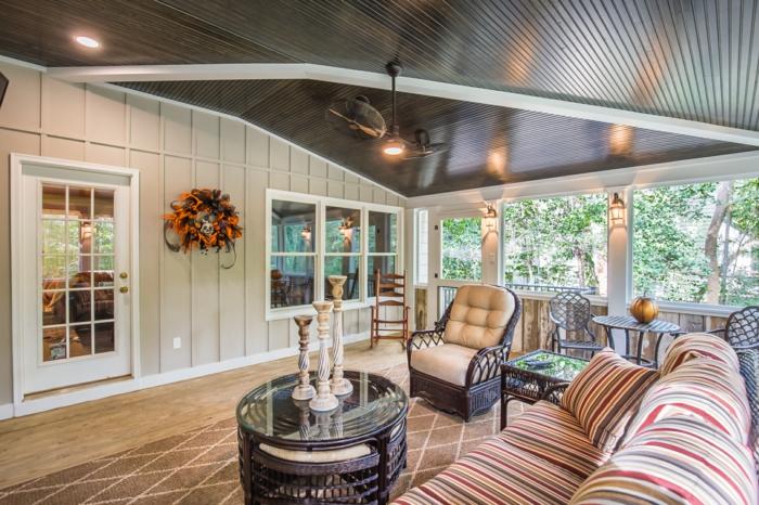 grand sofa rayé, table basse, fauteuil en bois, tapis géométrique, modele de veranda sur terrasse