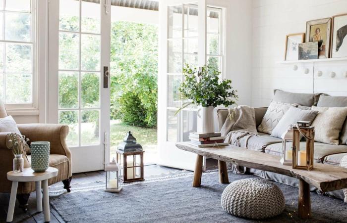 comment aménager un véranda, grande porte vitrée, tapis gris, pouf tricoté, lanternes au sol, table en bois brut, sofa gris