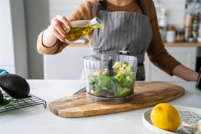 verser l huile d olive dans les feuilles de basilic, les cubes d avocat et le noix de cajou, recette avocat en entrée, recette pesto basilic