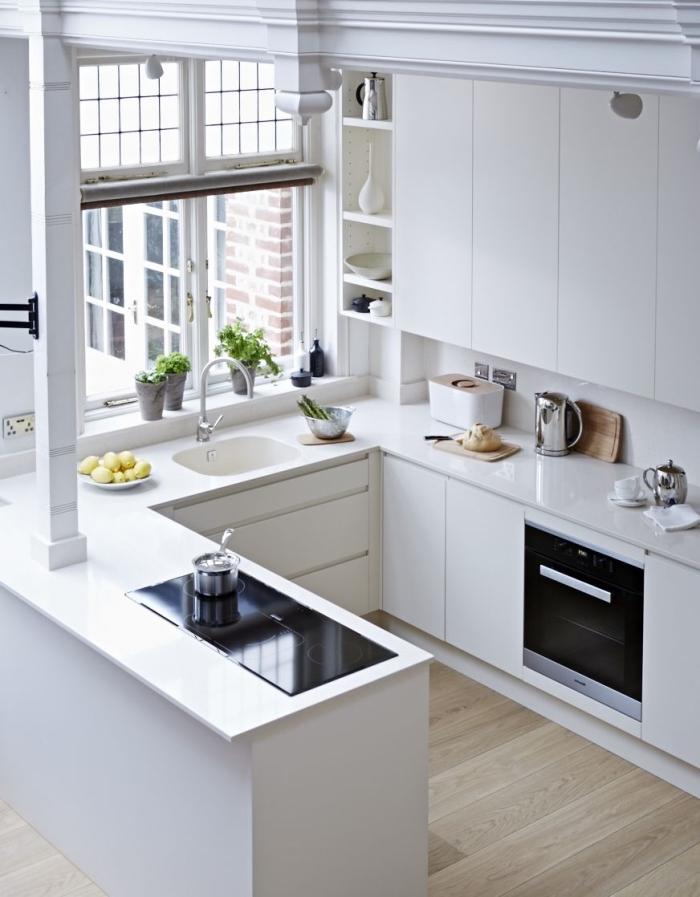 cuisine total blanc au plancher bois avec fenêtre et four noir, exemple de cuisine en u avec bar, idée rangement vertical ouvert