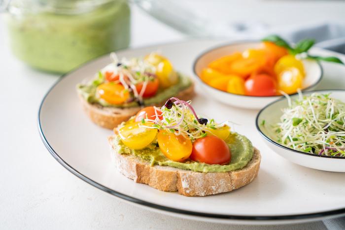 amuse bouche simple et bon, toast apero avec pesto à l avocat et basilic décoré de tomates-cerise et graines germées