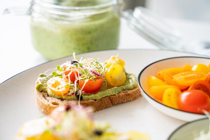 idee comment faire recette pesto basilic comme aperitif dinatoire froid avec avocat, tartines décorées de tomates cerise, graines germées