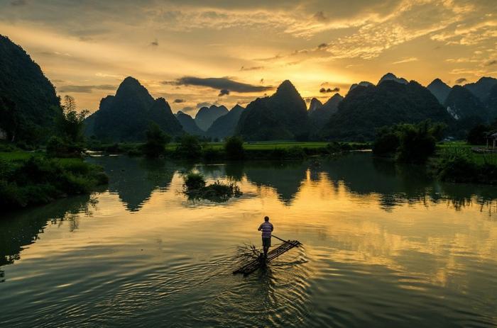 joli après-midi, un homme qui nage dans un lac entouré des sommets des montagnes