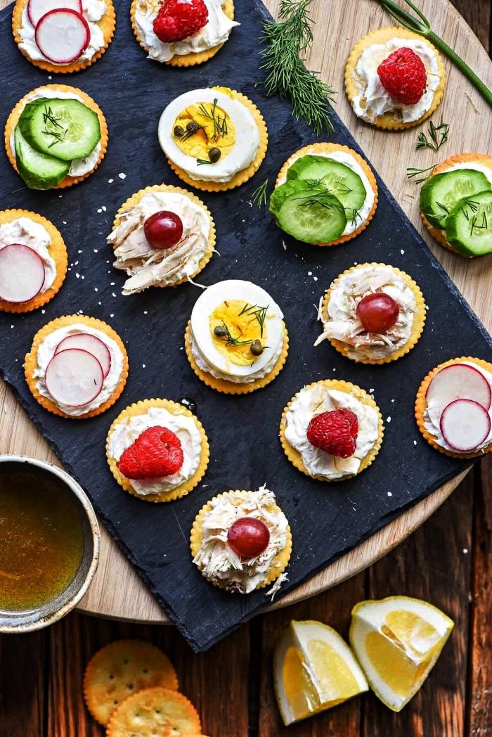 assortiment de canapés de crackers au fromage à la crème garnis de radis, concombres, oeufs durs ou framboises, assortiments de bouchées pour un apéro dinatoire froid rapide