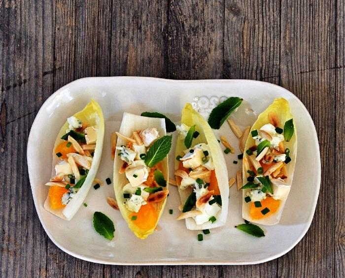 un plateau de barquettes d'endives à l'orange, amandes et fromages, recette végétarienne apéro dinatoire pas cher original