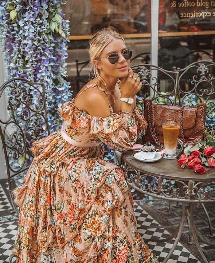 Belle femme en robe fleurie longue à manche longue avec épaules dénudées, lunettes de soleil rondes, café à londres, table ronde en metal, bouquet de fleurs