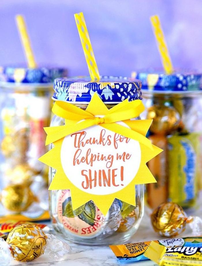 pot en verre rempli de gourmandises, bonbons, petits chocolats dans un bocal à boire avec paille et étiquette cadeau en forme de soleil