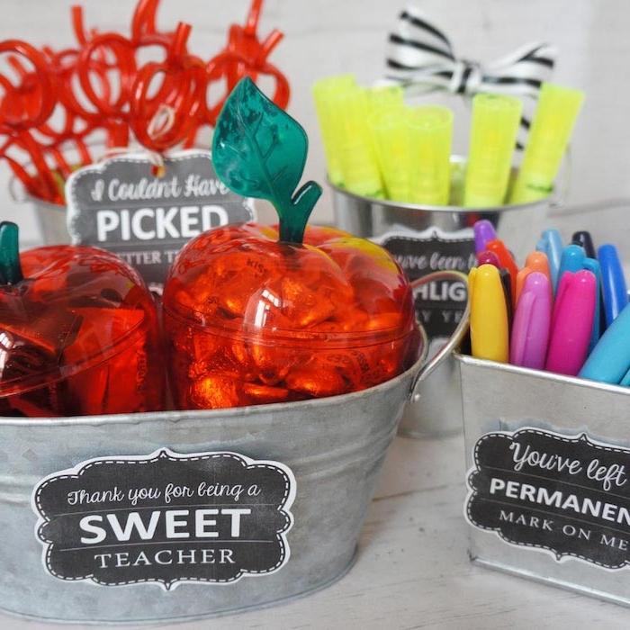 bacs à cadeaux avec des stylos rangés à l intérieur et de boites plastiques en forme de pomme avec bonbons à l intérieur
