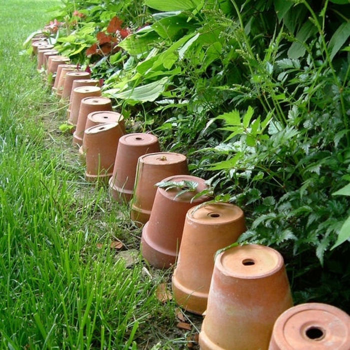 bordure en vieux pots d'argile, pelouse, parterre de plantes vertes, aménagement de jardin original