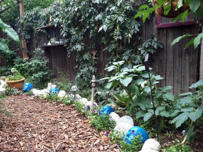 cloture en bois, bordure originale de bornes en forme de têtes, treillis de jardin, plantes grimpantes