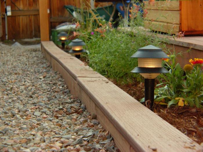 bordure de jardin en bois, lampes solaires près de l'allée de jardin en gravier, parterre de fleurs