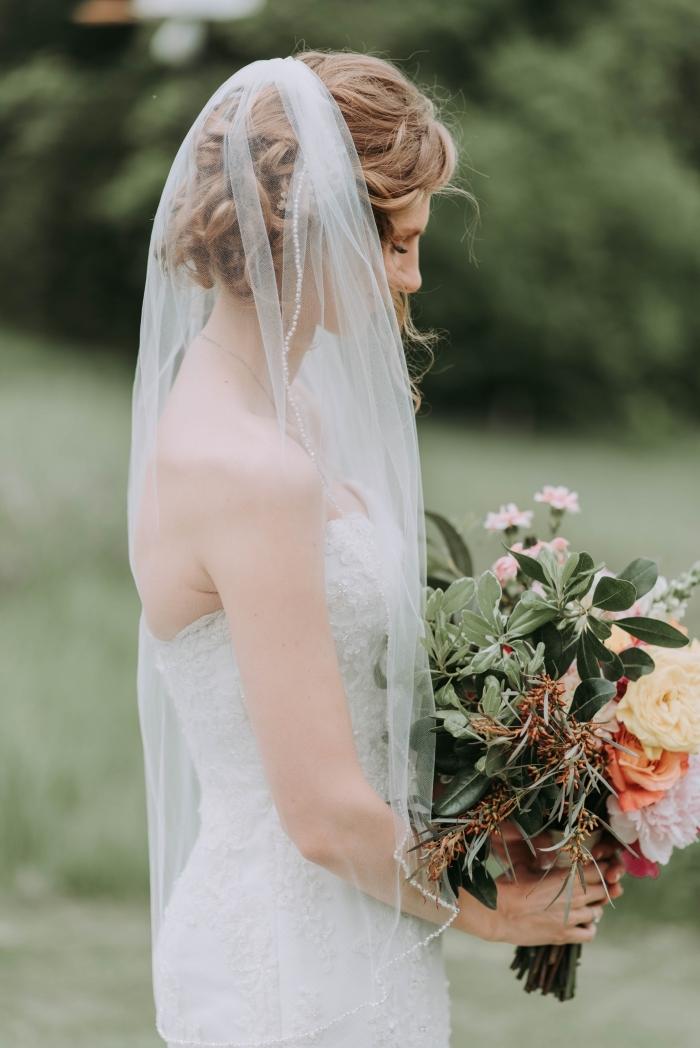 quelle coiffure cheveux longs attachés avec voile, idée coiffure de mariée romantique, modèle chignon mariage bas flou
