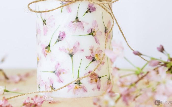 bougie décorée à pétales de fleurs collées dessus et une ficelle décorative simple en dessus