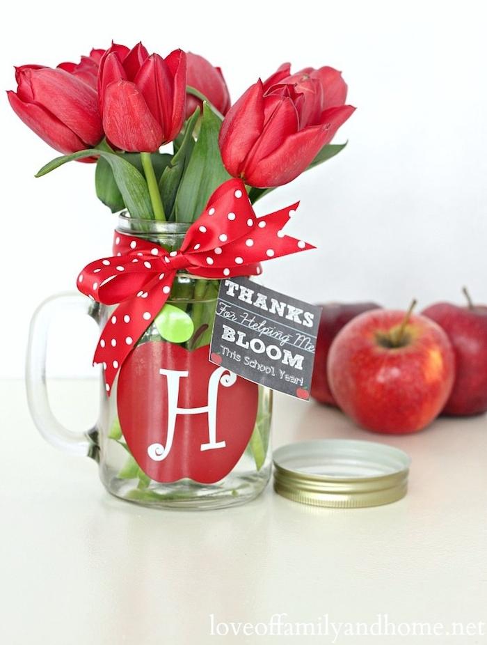 cadeau maîtresse école, idée de verre transformé vase de fleurs avec motif pomme rouge, symbole du savoir et de la sagesse et bouquet de tulipes