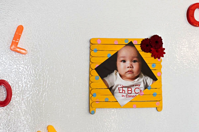 idée de petit cadeau fête des mères à fabriquer avec les enfants de l'école maternelle, cadre photo fait-maison en bâtonnets de bois peints en jaune à motifs pois