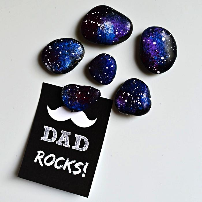 des cailloux personnalisés repeints aux couleurs de la galaxie à offrir comme cadeau fete des peres original, accompagné d'une carte moustache