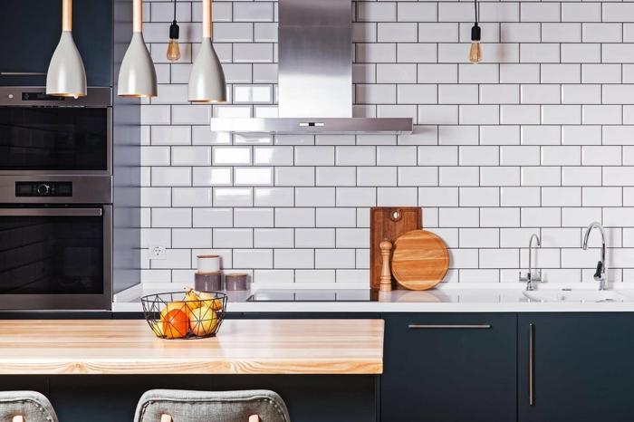 trois suspensions luminaires dans une cuisine, ilot de cuisine, chaise de cuisine, carreaux metro au mur