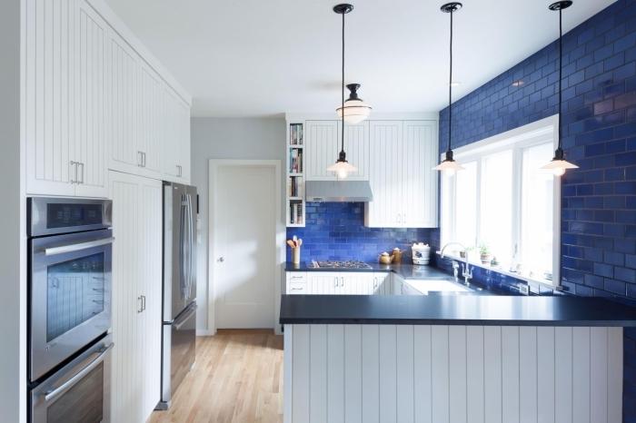 idée cuisine petit espace, décoration cuisine blanche avec carreaux bleu et plan de travail en noir, revêtement plancher cuisine en bois