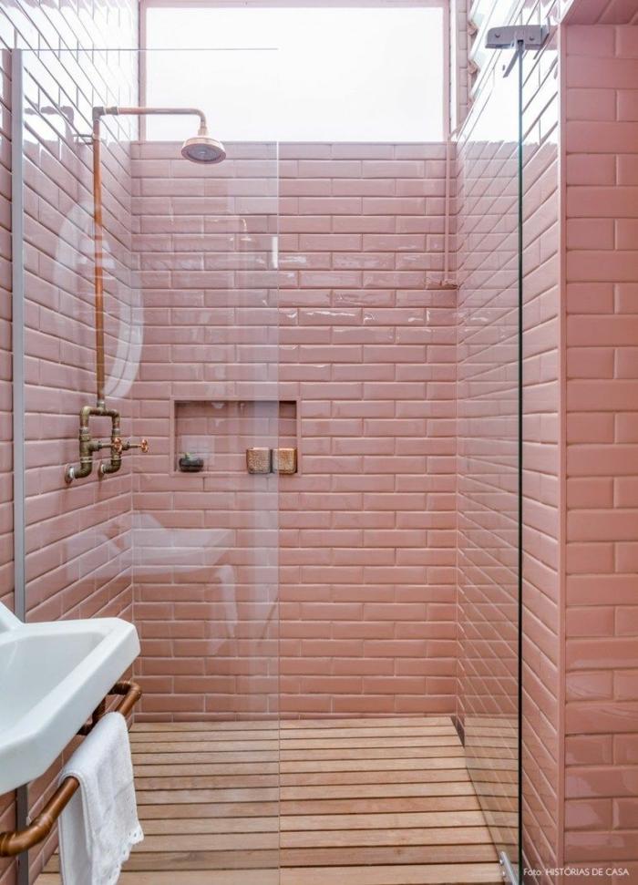carrelage mur rose, douche cuivrée, vasque suspendue blanche, revêtement du sol bois