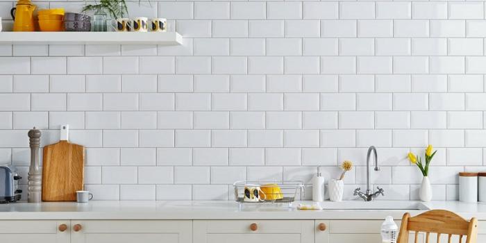 carrelage blanc brillant, placards blancs de cuisine, étagère blanche, chaise en bois, poignées en bois