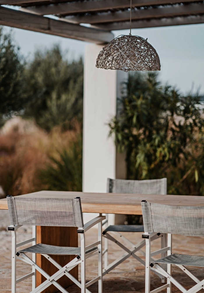 grande table de jardin en bois massif entourée de chaises pliantes, coin repas extérieur aménagé sous un pergola en bois