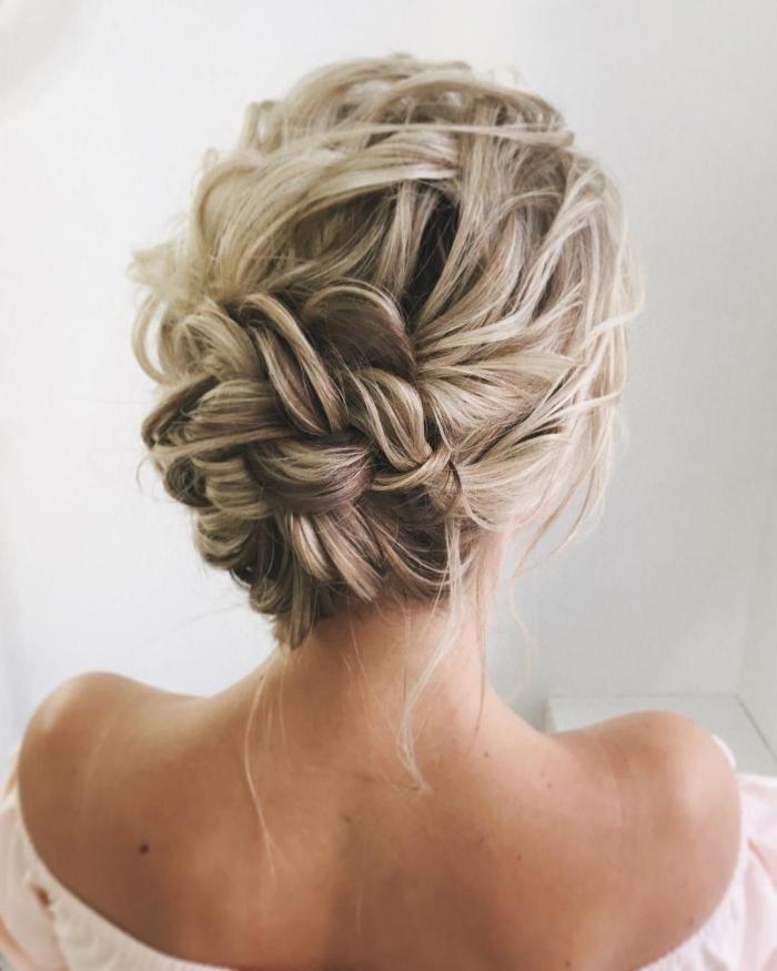 coiffure de mariage pour cheveux longs, modèle de chignon bas flou avec boucles tressées et mèches tombantes