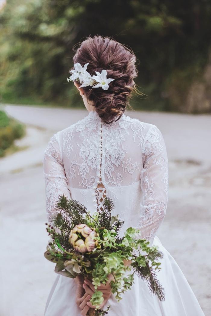 exemple de chignon mariage pour cheveux longs, modèle chignon bas tressé avec accessoire fleuri, idée robe mariée aux manches longues et dos boutonné