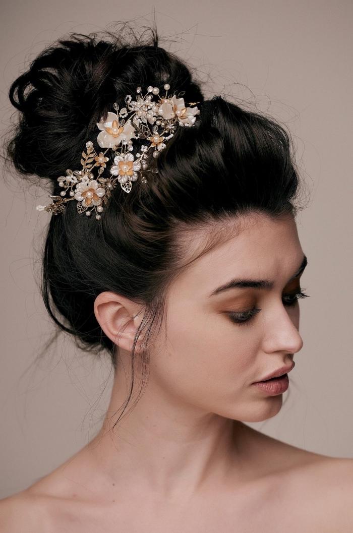 modèle de coiffure de mariage aux cheveux attachés en chignon bas flou avec branche fleurie, modèle de chignon cheveux long