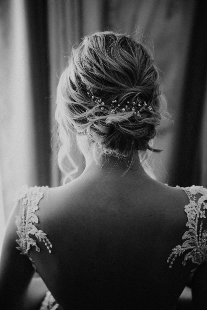 idée coiffure simple et romantique pour mariée, modèle de chignon bas flou avec boucles mèches tombantes