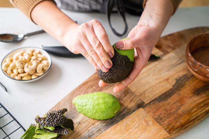 éplucher un avocat pour faire pesto noix de cajou, avocat, feuilles de basilic, recette apéro dinatoire facile sans cuisson