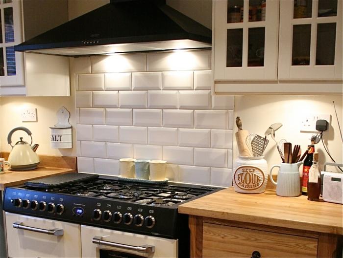 carrelage metro blanc, cuisinière, hotte de cuisine, placards en bois, crédence de cuisine classique