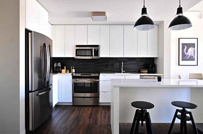 cuisine blanche de style contemporain équipée de placards sans poignées et d'un îlot central qui semble se fondre dans le décor