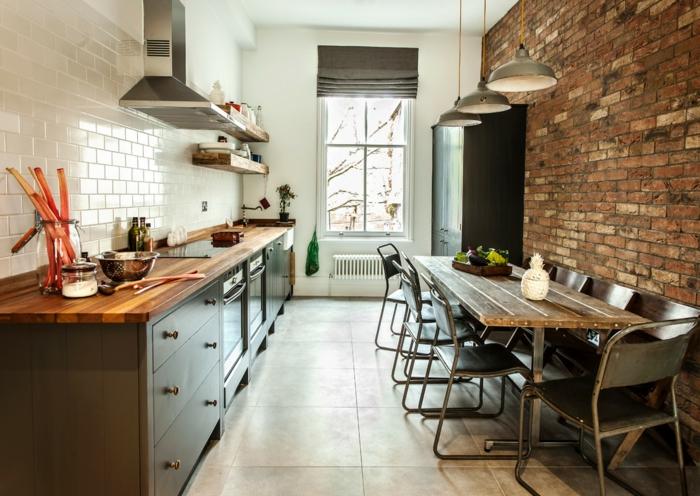 cuisine design industriel, placards de cuisine en bois, table en bois et métal, mur en briques rouges, carrelage metro blanc
