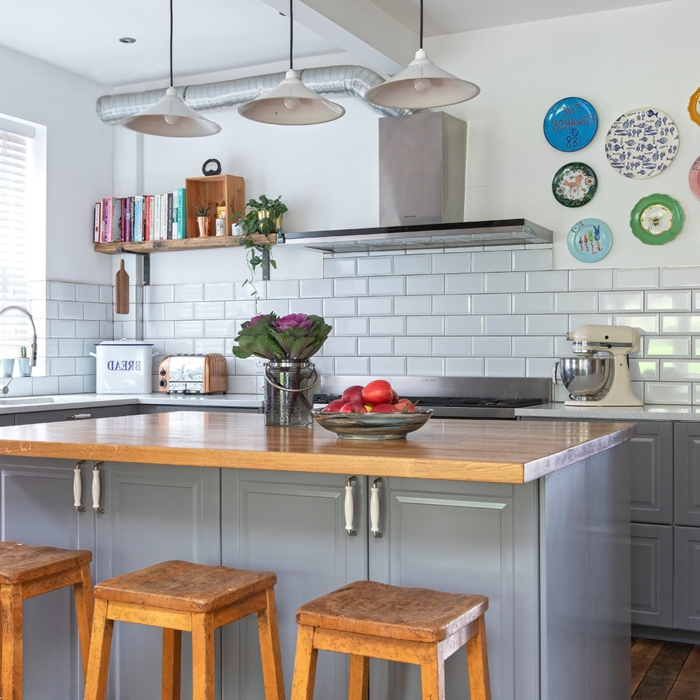 îlot de cuisine, carrelage métro blanc, lampes pendantes, étagère en bois brut, carrelage blanc brillant