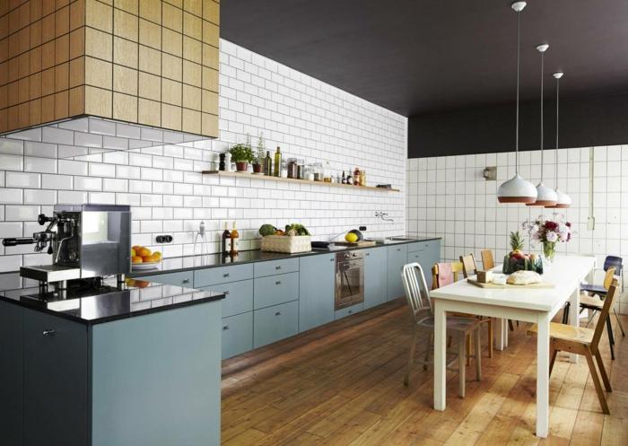 carrelage métro, armoires de cuisine bleues, grande table de repas, lampes pendantes, plafond noir