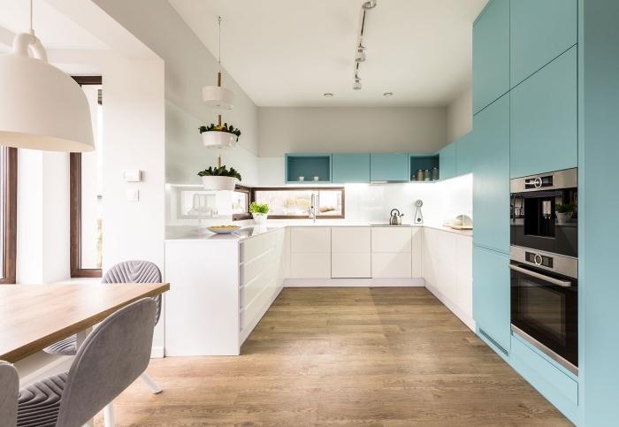exemple agencement cuisine spacieuse avec fenêtres, revêtement plancher de cuisine en bois, modèle armoires de cuisine en bleu
