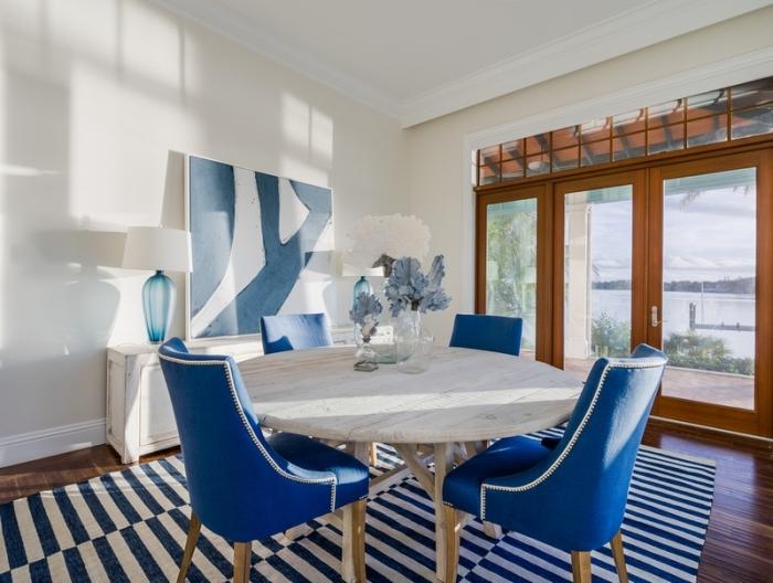 agencement salle à manger au plancher bois foncé avec meuble bois clair, modèle de chaise couleur bleu marine