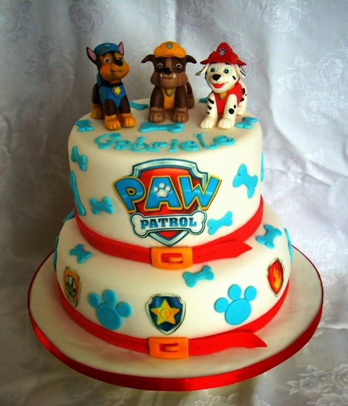 gateau anniversaire pat patrouille, décorations bleues, trois chiens policiers, pattes 3d, glaçage blanc